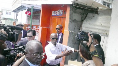 Donald Rodney (second from left) stands in front of the White Castle Fish shop, the exact location where his car was parked on the night of the explosion.