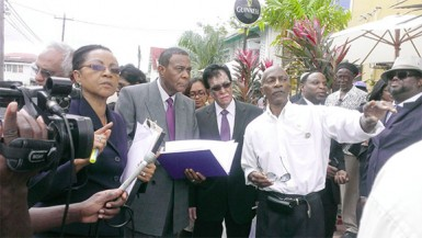 Donald Rodney (right) shows Commissioner Seenath Jairam (second right), Chairman of the Commission Sir Richard Cheltenham (centre) and Commissioner Jacqueline Samuels-Brown (left) the direction in which he ran after the explosion.