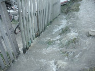 Water rushing into a resident's home when Stabroek News visited.