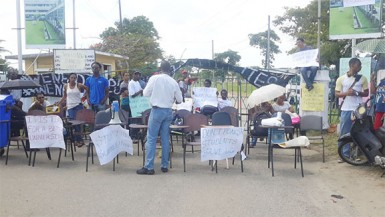 Students protesting in front of the main gate of the University of Guyana Turkeyen Campus.
