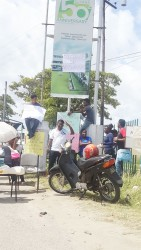 """University of Guyana students plastered the words """"All classes or no classes"""" on a billboard celebrating the university's 50th anniversary at the entrance of the Turkeyen Campus."""