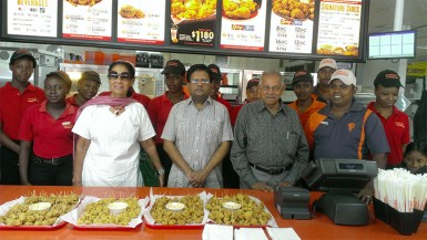 Finance Minister Ashni Singh (fourth from left) stands beside Chairman of Guyana Restaurant Incorporated, Raj L Singh (third from right) with staffs of the third Popeye's restaurant.