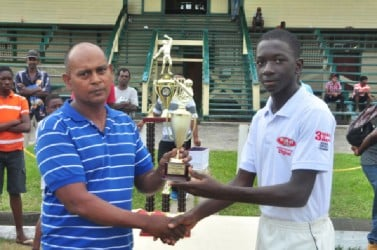 Player of the match Garfield Benjamin accepts his MVP trophy from Selector Nazimul Drepaul. (Orlando Charles photo)