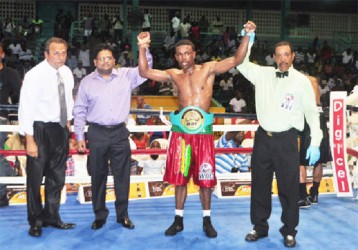Minister of Finance, Ashni Singh and referee Eon Jardine raises the hand of the newly crowned WBC CABOFE light welterweight champion, Clive Atwell as president of the GBBC, Peter Abdool looks on. (Orlando Charles photo)