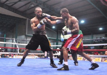 Clive 'The Punisher' Atwell (right) lands a right hand to the jaw of Sakima Mullings during part of their action packed bout on Saturday night at the Cliff Anderson Sports Hall. (Orlando Charles photo)