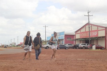 Brazilian shoppers walk in the Lethem Commercial Zone