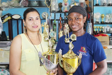 Devi Sunich (left) of the Trophy Stall presents the winning male and female trophies to Noshavyah King, the coordinator of the inaugural E-Networks Crossfit Games.