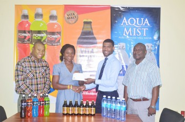 Aqua Mist Brand Manager Errol Nelson, presents a cheque to coordinator of the Games, Noshavyah King of Genesis Fitness Express while Troy Peters, Communications Manager of the local beverage giant and brand manager, Colin King look on.