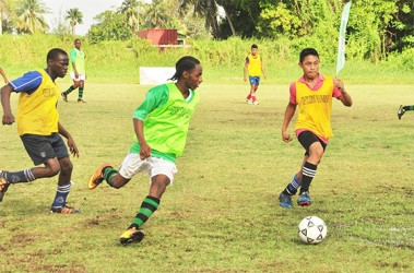 Jarel Grannum of Lodge Secondary (centre) on the attack while being pursued by two Cummings Lodge players during their teams' matchup