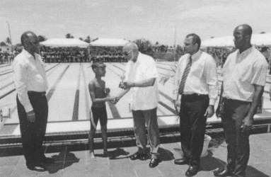 Director of Sports Neil Kumar, left, Dr. Frank Anthony, second right and Permanent Secretary Alfred King, right watches as President Donald Ramotar presents a trophy to the winner of an exhibition race at the newly commissioned Warm Up pool Friday at the National Aquatic Centre, Liliendaal. (photo courtesy of GINA)