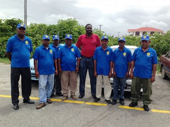 President of the United Minibus Union Eon Andrews (fourth, right) poses with the Tuschen Hire Car Service (THCS) drivers, who have kicked their service up a notch by being properly attired and easily identifiable. (Photo by Shabna Ullah)