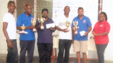 Mashramani draughts champion Khemraj Pooranmall, second right displays the first place trophy. Others in picture are from left, Esan Anderson, Mark Brathwaite, Jairam, Steve Bacchus and Marlyn Ali.