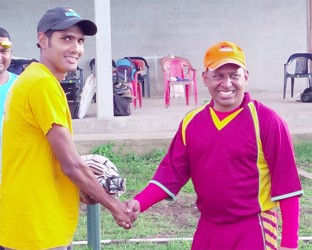 Proprietor of Tiger Sports and former national wicketkeeper/batsman, Sheik Mohamed (right), presents a pair of batting glove to Guyana Media XI opener, Ravi Persaud.