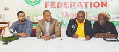 Jamaal Shabazz (3rd from left) in the process of inking his two year contract with the GFF Normalization Committee while Normalization Committee member Tariq Williams (left), Chairman Clinton Urling (2nd left) and Assistant coach Wayne Dover look on