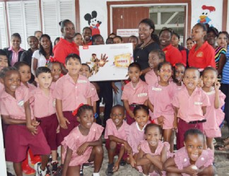 Elicia Chapman, Customer Service Officer of Massy Gas Products presents the television set to a teacher of Eccles Primary in the presence of pupils, teachers and parents. (Massy photo)