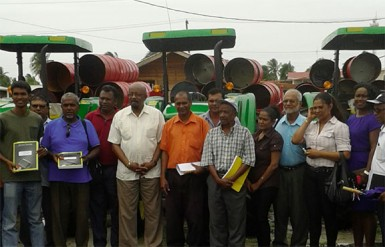 Minster Norman Whittaker stands with the overseers and chairpersons in front of the new tractors and trailers
