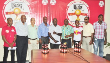 President of the GRFU, Peter Green (left) is all smiles yesterday as he received the sponsorship cheque from Banks DIH's Communications Manager, Troy Peters in the presence of the union's top brass. (Orlando Charles photo)