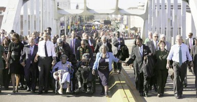 US President Barack Obama (3rd L) participates in a march across the Edmund Pettus Bridge in Selma, Alabama, March 7, 2015. Also pictured are first lady Michelle Obama (L), US Representative John Lewis (D-GA) (2nd L), former first lady Laura Bush (2nd R) and former president George W Bush (R). (Reuters/Jonathan Ernst)