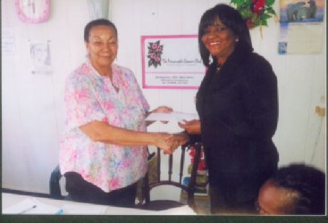 Director of the Periwinkle Club Luna Chung (left) receives the cheque for $1 million from Attorney Gem Sanford-Johnson (right).