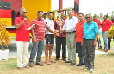 Last year's overall winner Alanzo Greaves receives the champion trophy from Minister of Sport Dr. Frank Anthony in the presence of race organizer Hassan Mohammed, Director of Sport Neil  Kumar and other stakeholders. (Orlando Charles photo)