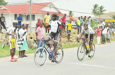 Team Evolution's Orville Hinds reacts after winning yesterday's 60-mile road race in Berbice. (Orlando Charles photo)