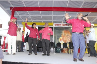 Ramotar does Bob Marley: President Donald Ramotar (right) rendering his version of `every little thing gonna be alright' at yesterday's PPP/C observance at Babu John, Port Mourant for the Jagans. His chorus comprised from left, PPP General Secretary Clement Rohee, prime ministerial nominee for the upcoming elections, Elisabeth Harper and Prime Minister Samuel Hinds. (Arian Browne photo)