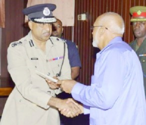 Police Commissioner Seelall Persaud (left) receiving his instrument of appointment from President Donald Ramotar. (GINA photo)