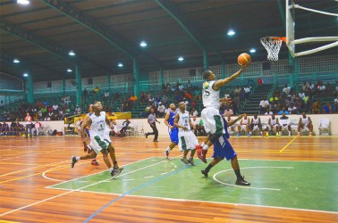 Guyana's Shelroy Thomas (#15) in the process of scoring a lay-up while being challenged by John Lee of Bermuda during his side's historic victory