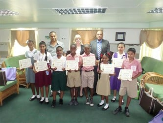 The winning children with (from right in back row) Speaker, Raphael Trotman, UNICEF Representative Marianne Flach and artist, Philbert Gajadhar.