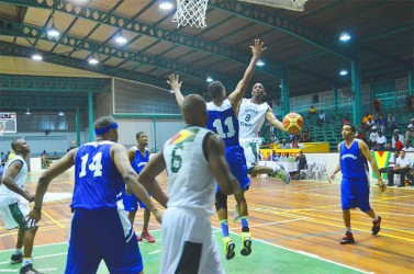 Travis Burnette (#8) of Guyana attempting to score a lay-up while trying to evade the outstretched hands of Bermuda's Jason Lowe (#11) during the opening match of their three-game international series