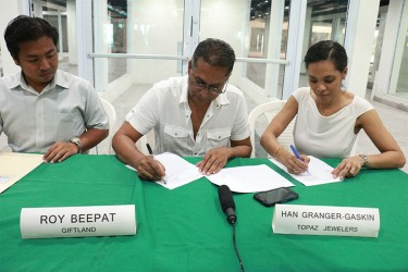 Giftland's Roy Beepat (centre) and Topaz's Han Granger-Gaskin signing contract.