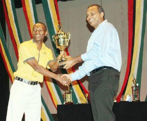 Roger 'Young Bill Rogers' Hinds (left) receives his winning trophy from Minister of Culture Frank Anthony.