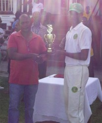 Demerara skipper Ronaldo Ali-Mohamed receives the winning trophy from chairman of the junior selection panel Sauid Drepaul.