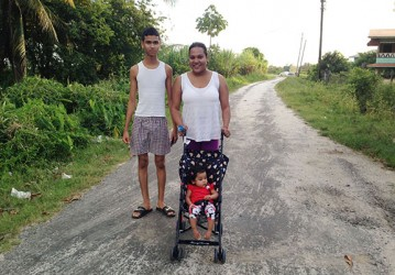 Chitra Devonish and her brother, Dinesh take a walk with her baby.