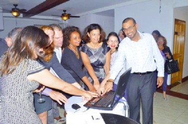 Minister of Natural Resources and the Environment, Robert Persaud (right) and United Nations Resident Representative to Guyana, Khadija Musa (fourth from right) and representatives of other countries press the button to launch the Guiana Shield Priority Setting Platform. (GINA photo)
