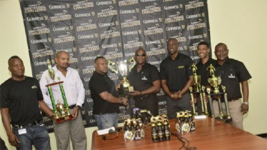 Tournament Coordinator Troy Mendonca (third from left) receiving the championship trophy from Banks DIH East Coast Area Manager Clive Pellew while other members of the launch party inclusive of Guinness Brand Manager Lee Baptiste (third from right) looks on.