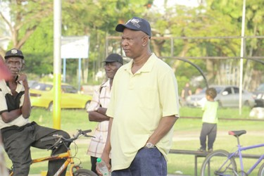 Clifford Crum-Ewing (right), the father of murdered political activist Courtney Crum-Ewing listening to a speech yesterday. A `silent' vigil was held in honour of the father of three at the Parade Ground. During the event several persons addressed the approximately 250 persons who had gathered calling on them to condemn the killing and to ensure that they vote come May 11. (Photo by Arian Browne)