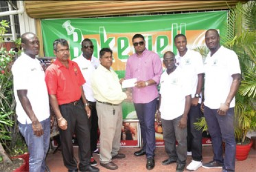 Slingerz FC owner and President Javed Ali (fourth from right) receiving the sponsorship cheque from Bakewell General Manager Rajin Ganga while other members of the club look on.