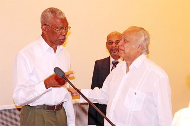 Presidential candidate David Granger (left) shares a moment with Sir Shridath Ramphal during Tuesday's forum at the Pegasus Hotel.