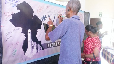 People signing the 'Vote Like A Boss' banner yesterday at the Guyana National Youth Council launch of the voters education campaign.