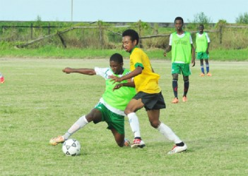 Keith Caines of Chase Academy (right) on the attack while being pursued by his Queenstown Secondary marker during his side's quarterfinal victory