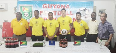 Newly recruited Golden Jaguars Neil Danns (3rd from left) and Matthew Briggs (4th from left) posing for a photo opportunity with members of the national team staff and Banks DIH Limited inclusive of head-coach Jamaal Shabazz (left) during their presentation to the media