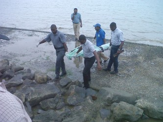 The body of Alicia Alli being retrieved from the seawall yesterday.