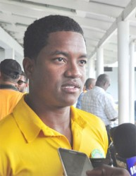 Leon Johnson speaks with reporters on landing at the CJIA after the Guyana Jaguars won the Regional 4-day title