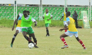 Chase Academy goal-scorer Marlon Nedd (green) battling to maintain possession of the ball while being challenged by two Morgan Learning Centre players during their team's semi-final showdown