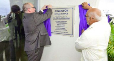 President Donald Ramotar (right) and a Qualfon official unveiling the plaque to the Qualfon campus at Providence yesterday. (GINA photo)