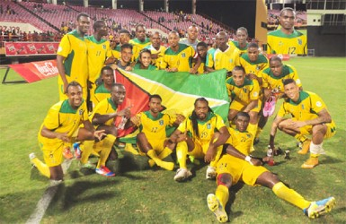 The victorious Golden Jaguars team after their 2-0 defeat of Grenada last night at the National Stadium, Providence. Inset Pernell Schultz. (Orlando Charles photos)