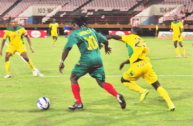 Grenada's Kithson Bain being challenged for possession by a Golden Jaguars player.  (Orlando Charles photo)
