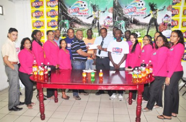 Tournament Coordinator Troy Mendonca (centre) receiving the championship trophy from Guyana Beverage Company Managing Director Robert Selman while members of the company and several representatives of the competing teams look on.