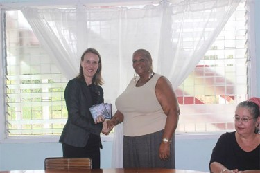 High Commissioner of Canada Dr Nicole Giles (left) hands over DVDs featuring discourses on sexual violence to Rainbow House representative Namela Henry